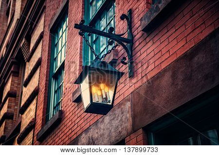 Black old vintage lamp on brick wall with decorative candels inside at old town house. House decoration concept.