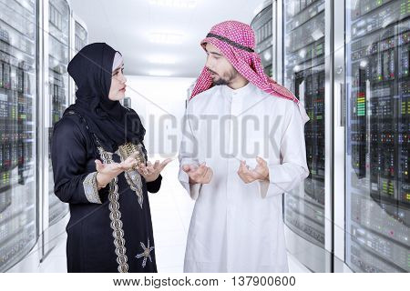 Picture of two Arabian businespeople discussing together in the server room