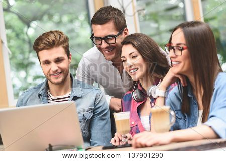 What do you think. Group of friends hanging out in coffee shop with laptop amongst them