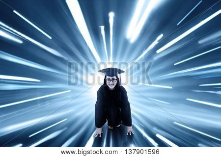 Female college student wearing mortarboard and ready to run with fast motion blur background