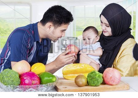 Portrait of happy young family and their baby cooking healthy food together in the kitchen