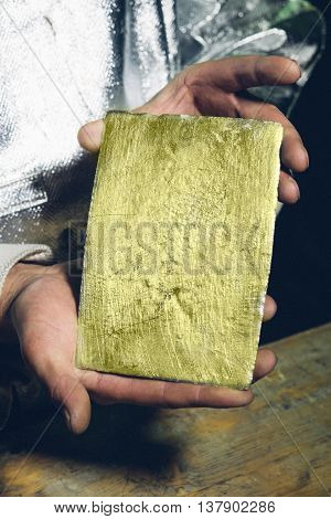 Raw gold ingot in hands just made at a factory poster