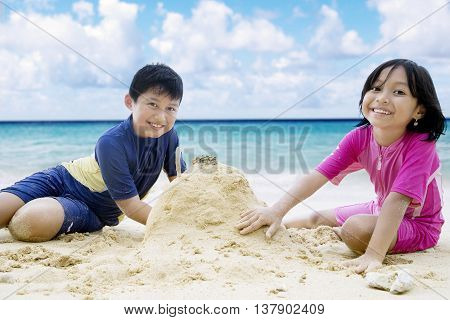 Portrait of two happy children smiling at the camera while making sandcastle at the beach
