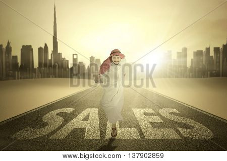Photo of middle eastern entrepreneur running on the highway with Sales word and wearing islamic clothes