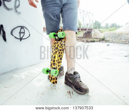 young handsome real hipsrter guy bearded staying under the bridge extreeme with leopard skateboard, lifestyle cool summer people concept