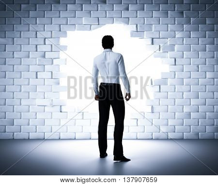 Businessman standing next to a hole in a brick wall. Light coming from outside. Concept of a change, new career, breaking the obstacle. 3D rendering