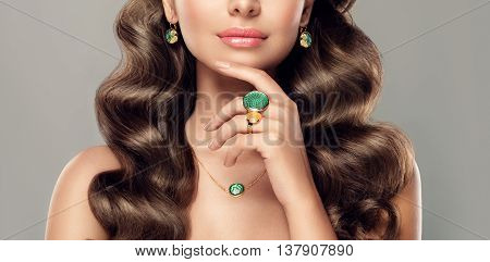 fashion woman  model with jewelry . girl with curly long hair and fashionable jewelry , earrings  and ring
