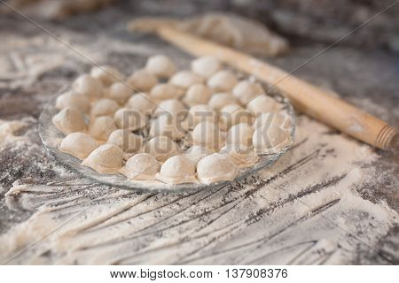 Raw homemade russian food - dumpling. Their in flower and have traditional form. Placed on the plate. Pork chicken mincemeat. Background table in kitchen. Wooden plunge.
