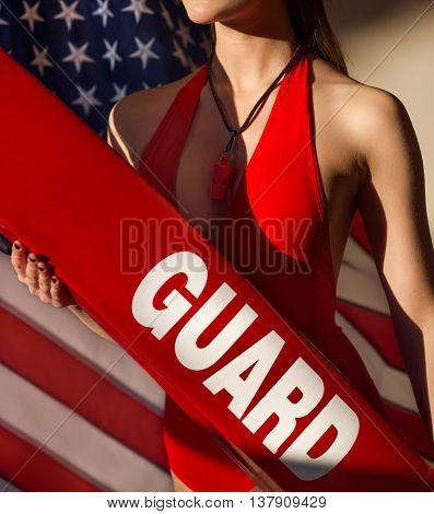 American woman lifeguard with resque tube and whistle equipment against USA flag