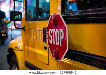 Stop sign on side on yellow School Bus
