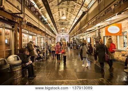 NEW YORK CITY - FEBRUARY 27: People on shopping at Chelsea Market. It is an enclosed urban food court shopping mall office building and television production facility on February 27 2016 in New York City USA