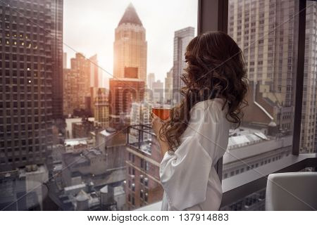 Beautiful woman holding coffee cup and looking to the window in luxury Manhattan penthouse apartments. Good morning after wake up. poster
