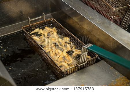 shrimpins in breadcrumbs cooking on deep fryer