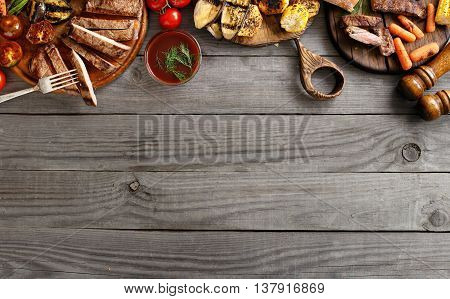 Grilled beef steak with grilled vegetables on wooden table with copy space. Top view. Food Grill background