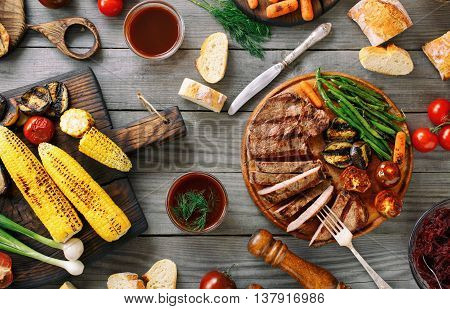 Juicy sliced grilled beef steak with various grilled vegetables on wooden table. Top view. Outdoors Food Concept