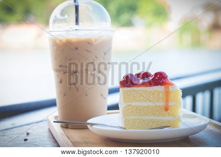 Sponge cake with cherry syrup. Peace of cherry cake serve with iced coffee. Cherry cake in cozy outdoor cafe.
