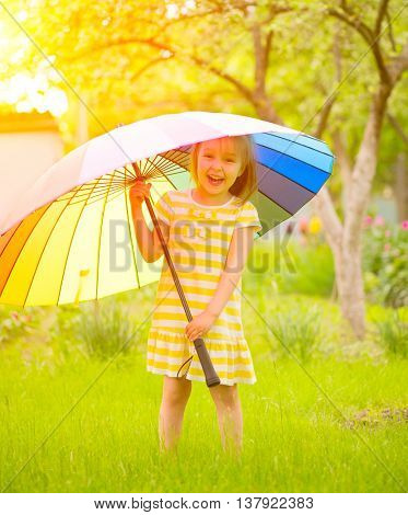 Portrait of a smiling little girl staying on green grass under the colorful umbrella. Cute child enjoying nature outdoors. Healthy carefree kid playing outside in summer park. Suntan protection