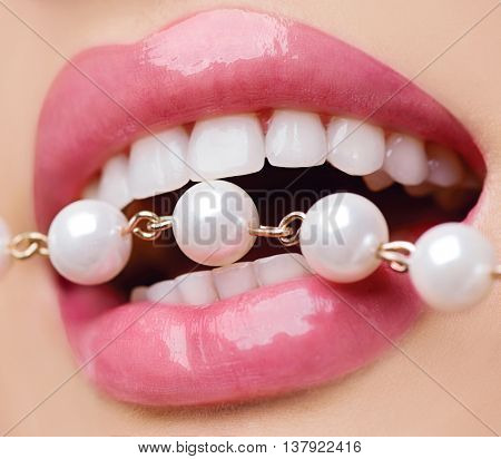 Beautiful woman teeth and lips, healthy white smile, beauty model girl mouth with pearls necklace close up. Oral care, teeth whitening concept. Lip Fillers, Plastic surgery