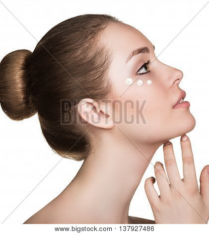 Beautiful model applying cosmetic cream dots on her face isolated on white