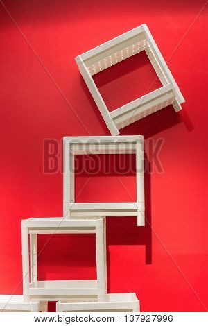 The White Stackable chairs with red walls.