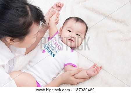 Portrait of beautiful mom playing with her 6 months old baby in bedroom top view