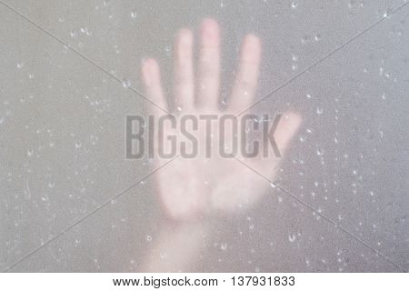 Palm hand behind frosted glass with droplets