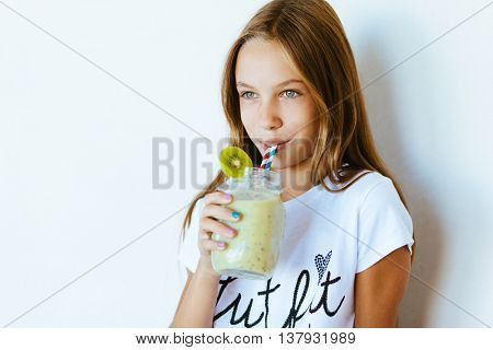 Beautiful teenage girl drinking smoothie shake against white wall
