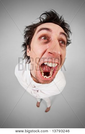Fish eye shot of screaming insane man in strait-jacket on grey background
