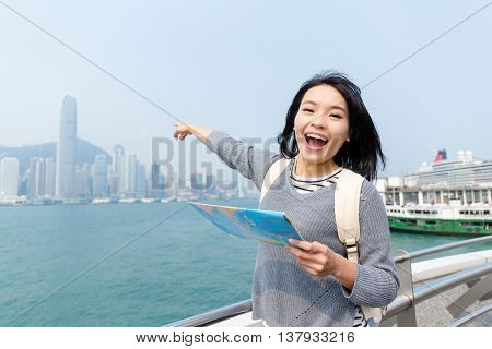 Woman pointing far away with paper map