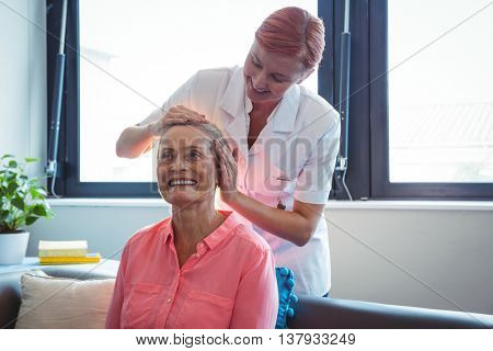 Nurse giving head massage to senior woman in a retirement home