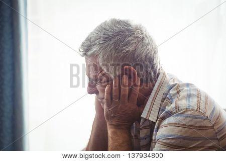 Sad senior man sitting in a retirement home