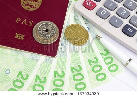 Danish Kroner notes in a passport with a calculator and pen.
