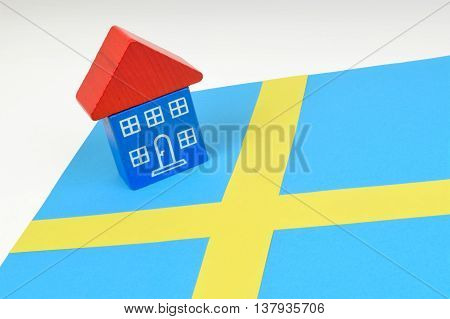 A toy house sitting on a Swedish flag. A still life on the Swedish property market.