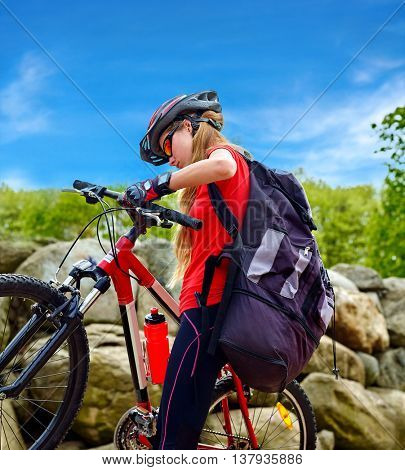 Bikes bicyclist girl. Girl rides bicycle into mountains. Girl on bicycle in mountaineering . Girl carries her bike over rocks. Bicyclist looks at his feet aganist blue sky.