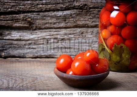Foto of canned tomatoes on wooden background