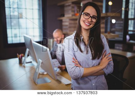 Portrait of confident businesswoman standing by desk while male colleague in background at creative office