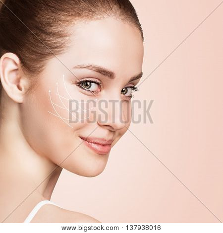 Young female face with clean fresh skin over biege background. Antiaging concept