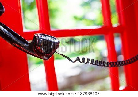 handset in the red telephone box. black telephone handset is hung in the air. it would take someone to call or handset will fall and hang on a telephone wire. concept of communication
