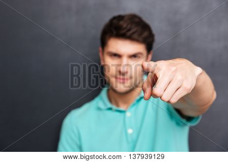 Close up portrait of a handsome man pointing finger at camera isolated on a black chalkboard, focus on finger