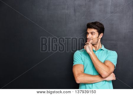 Happy thoughtful young man standing with hands folded and looking away over chalkboard background