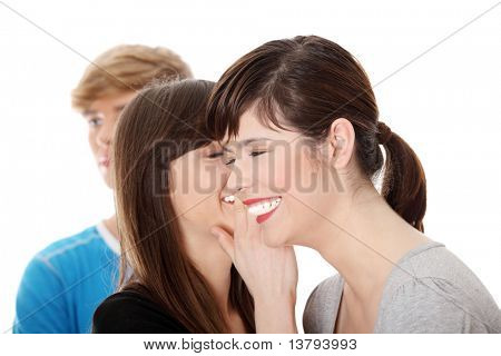 Two girls talking (gossip) about boy, isolated on white