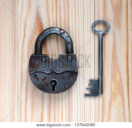 Padlock and key on a wooden background.