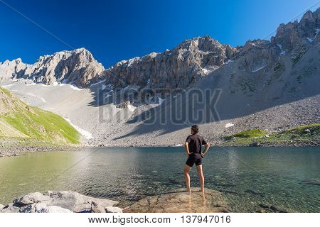 Hiker Relaxing At High Altitude Blue Lake In Idyllic Uncontaminated Environment Once Covered By Glac