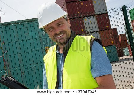 Happy Man Logistics Manager At Container Transhipment Plant, With An Electronic Tablet