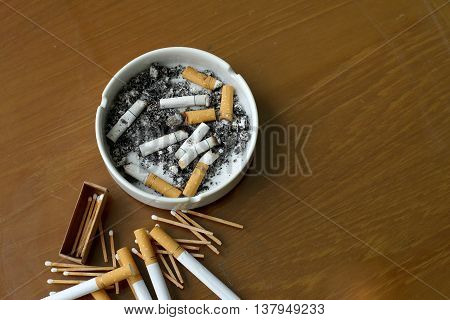 Smoked Cigarettes In White Ashtray And Matchstick