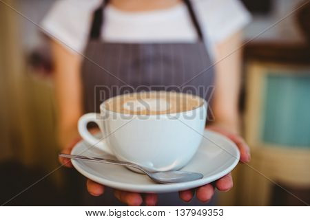 Midsection of female barista serving coffee at cafeteria
