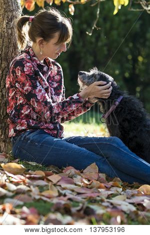 Woman sitting under a tree amongst autumn leaves fondling her pet dog holding its face tenderly between her hands.