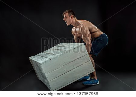 Young Muscular man flipping box. Cross-fit exercise