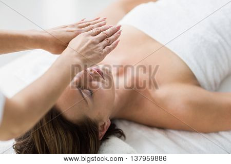 Thearapist performing reiki on young woman at spa