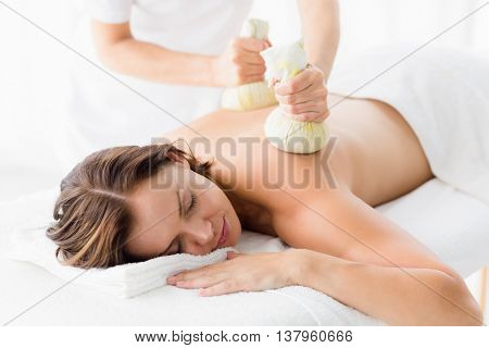 Naked woman receiving herbal compress massage at spa
